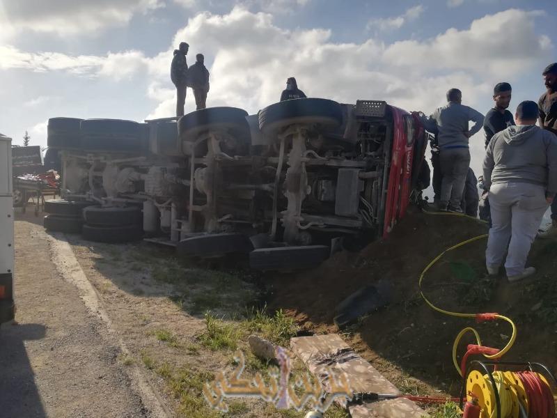 محاولات انقاذ شخصين بعد انقلاب شاحنة عند مدخل العيشية